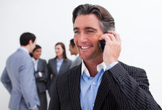 Manager on phone with his team in the background Stock Images