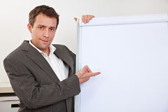 Manager pointing to empty flipchart Stock Image