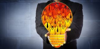 Manager Presenting Lightbulb of Virtual Workforce. Unrecognizable corporate manager offering a virtual talent pool shaped like a light bulb filled with employee Royalty Free Stock Photos