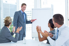 Manager presenting whiteboard to his colleagues Stock Image