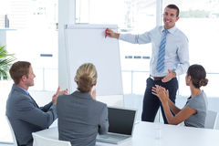 Manager presenting whiteboard to his colleagues. In the office stock photography