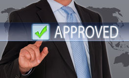 """Manager pressing tick on touch screen. Manager in smart business suit, blue shirt and tie pressing the green tick box marked """"approved"""" on a touch screen, world Royalty Free Stock Images"""