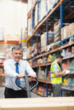 Manager pulling trolley with boxes in front of his employee Royalty Free Stock Photos