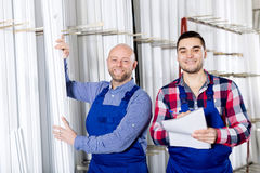 Manager at PVC windows factory. Happy young manager approving employee work at PVC windows factory stock photography