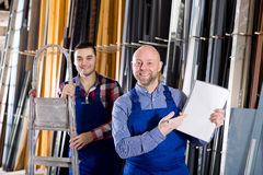 Manager at PVC windows factory. Portrait adult manager approving employee work at PVC windows factory royalty free stock photos