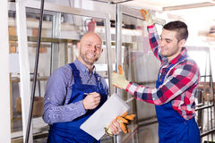 Manager at PVC windows factory. Satisfied manager approving employee work at PVC windows factory. Focus on the left man stock photography