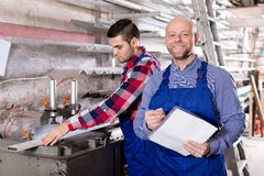 Manager at PVC windows factory. Satisfied manager and worker approving work at PVC windows factory royalty free stock photos