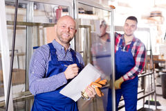 Manager at PVC windows factory. Smiling manager approving employee work at PVC windows factory stock image
