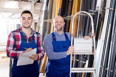 Manager at PVC windows factory. Young manager approving employee work at PVC windows factory royalty free stock photo