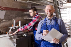 Manager at PVC windows factory. Manager and young worker approving work at PVC windows factory royalty free stock photo
