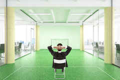 Manager relaxes during work day in the office with football fiea. Ld Stock Image