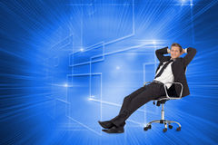 Manager relaxing in office with team in background Royalty Free Stock Images