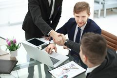 Manager`s and client`s handshakes over the Desk in the Bank`s office.  royalty free stock images