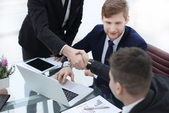 Manager`s and client`s handshakes over the Desk in the Bank`s office.  stock photos