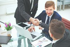 Manager`s and client`s handshakes over the Desk in the Bank`s office.  stock photo