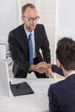 Manager sagt zu einem Kandidaten in einem Vorstellungsgespräch mit handsh Guten Tag Lizenzfreie Stockfotografie