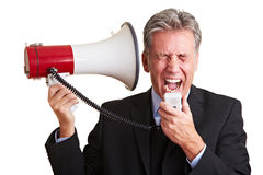 Manager screaming in megaphone. Elderly business man screaming loudly in a megaphone Stock Images