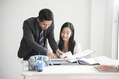 Manager and secretary consult for working in the office. Desk Stock Photography