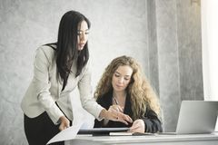 Manager and secretary consult for working in the office. Manager and secretary consult for working in the office desk Royalty Free Stock Images