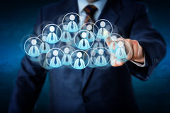 Manager Selecting Human Resources In The Cloud. Torso of a manager in blue business suit selecting white color worker icons in a virtual cloud shaped of many Stock Photo