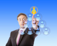 Manager Selecting A Male Worker Atop A Pyramid. Gazing business man is singling out the only one male worker icon atop a pyramid otherwise shaped by female white Royalty Free Stock Photos