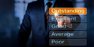 Manager Selecting Outstanding Button. Manager is selecting Outstanding atop five buttons, followed by Excellent, Good, Average and Poor. Business concept for Royalty Free Stock Image