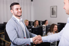 Manager shaking hand of employee Stock Image