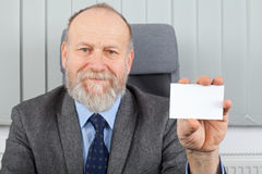 Manager showing business card. Picture of an elderly manager showing his business card at the office Stock Image