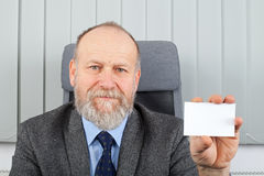 Manager showing business card. Picture of an elderly manager showing his business card at the office Royalty Free Stock Photography