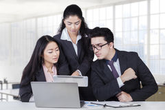 Manager showing business plan at team. Portrait of young business leader showing business plan on tablet at her team in the business meeting Royalty Free Stock Image