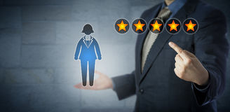 Manager Showing Female Employee With Five Stars. Blue chip manager is pointing at the five star rating of a female white collar worker. Human resource management Royalty Free Stock Photos