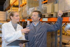Manager showing shelves to worker in warehouse Royalty Free Stock Photo