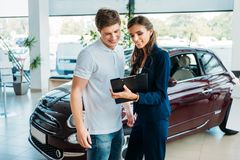 Manager showing something on a clipboard to the customer. In car showroom stock image