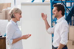 Manager showing something to his colleague on whiteboard. In a large warehouse Royalty Free Stock Photos