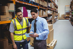 Manager showing tablet to worker. In warehouse Royalty Free Stock Photography