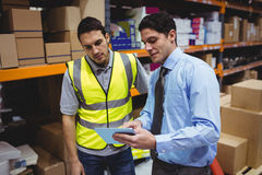 Manager showing tablet to worker. In warehouse Royalty Free Stock Images