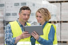Manager showing tablet to worker in warehouse Stock Photos