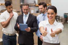 Manager showing thumbs up in front of her colleagues Royalty Free Stock Images