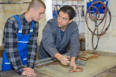Manager showing trainee how to work with blowtorch stock image