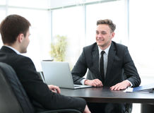 Manager sits behind the Desk and talks to the client Royalty Free Stock Photography