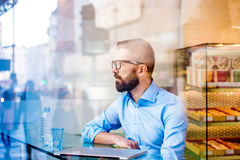 Manager sitting in cafe by the window, drinking water Stock Images
