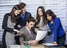 Manager sitting at the desk, surrounded by his business team Stock Photo