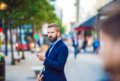 Manager with smartphone listening music outside in the street Royalty Free Stock Image