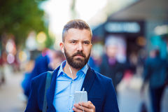 Manager with smartphone listening music outside in the street Stock Image