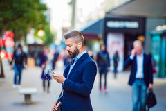 Manager with smartphone listening music outside in the street Stock Photography