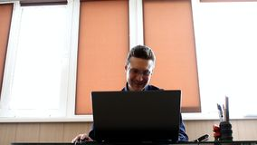 Manager smiling at the computer. Businessman laughing. Manager at the computer. Businessman working with laptop. Businessman working with computer in modern stock video footage