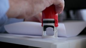 Manager Stamping Some Papers and Documents Using a Rubber Stamp in Slow Motion