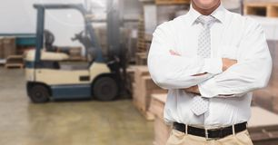 Manager standing with arms crossed in warehouse. Mid section of manager standing with arms crossed in warehouse Stock Images
