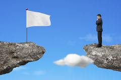Manager standing on cliff with blank white flag and sky Stock Photos