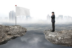 Manager standing on cliff with white flag and cloudy cityscape Royalty Free Stock Image